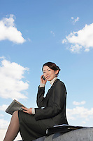 Businesswoman sitting outdoors Using Cell Phone reading newspaper low angle view