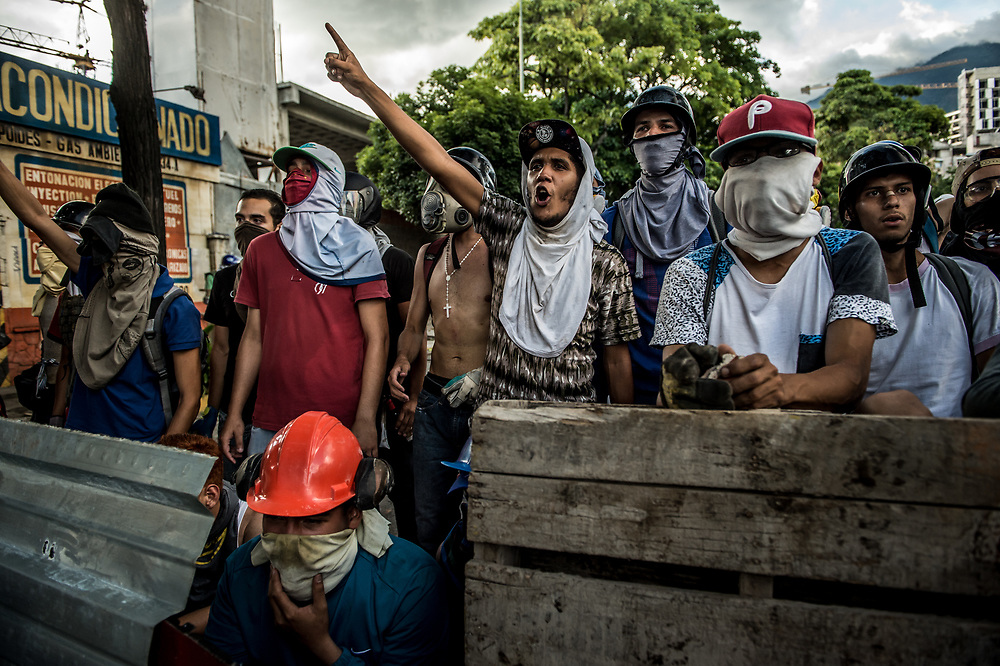 CARACAS, VENEZUELA - JULY 26, 2017: Members of La Resistencia sing the National Anthem, while taking refuge behind a street barricade that they built during clashes with soldiers during an anti-government protest to demand that the National Constituent Assembly election scheduled for Sunday, July 30th be cancelled. The political opposition called for a 48 hour national strike on July 26th and 27th, and for their supporters to close businesses, not go to work, and instead create barricades to block off their streets.  Opposition controlled areas of the country were completely shut down.  The strike was called as part of the opposition's civil resistance movement - that began on April 1st, to protest against the Socialist government's attempt to elect a new assembly that will have the power to re-write the constitution, and their opposition to the Socialist's continued threats to Venezuelan Democracy.  PHOTO: Meridith Kohut for The New York Times