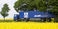 Europe, Germany, North Rhine-Westphalia, Ruhr area, street through rape fields between Essen and Bochum, truck of the company ALDI Nord [the supermarkets of Aldi will be supplied daily with food]. ....Europa, Deutschland, Nordrhein-Westfalen, Ruhrgebiet, Strasse durch Rapsfelder zwischen Essen und Bochum, LKW der Firma ALDI Nord [die Supermaerkte von ALDI werden taeglich mit Lebensmittel beliefert].