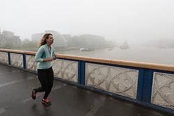 © Licensed to London News Pictures. 11/05/2016. LONDON, UK.  An early morning jogger crosses Tower Bridge in London during foggy and wet weather this morning.  Photo credit: Vickie Flores/LNP