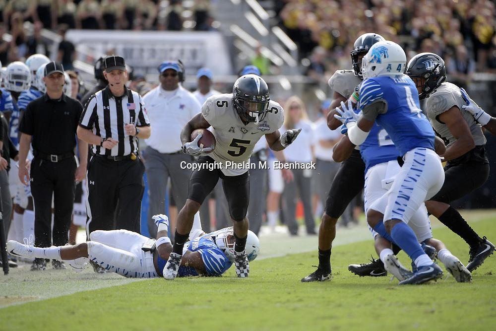 Central Florida wide receiver Dredrick Snelson (5) runs between Memphis defensive back Jonathan Cook (14) and defensive back Josh Perry (4) after catching a pass during the first half of the American Athletic Conference championship NCAA college football game Saturday, Dec. 2, 2017, in Orlando, Fla. (Photo by Phelan M. Ebenhack)