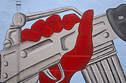 On a brick wall is a painted red hand that grips an Armalite automatic weapon which has been painted on to a street wall of a house off the protestant Shankhill Road in Belfast, Northern Ireland. The red hand is actually better-known as The Red Hand Defenders (RHD),  a Northern Irish paramilitary group formed in 1998 and composed largely of Protestant hardliners from loyalist groups observing a cease-fire. It is composed of members of the Ulster Defence Association (largely those who once belonged to the now disbanded 2nd Battalion, C Company) and Loyalist Volunteer Force, most of whom are still part of the latter organisation.