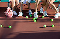 Scattered tennis balls on tennis court by feet of family low section