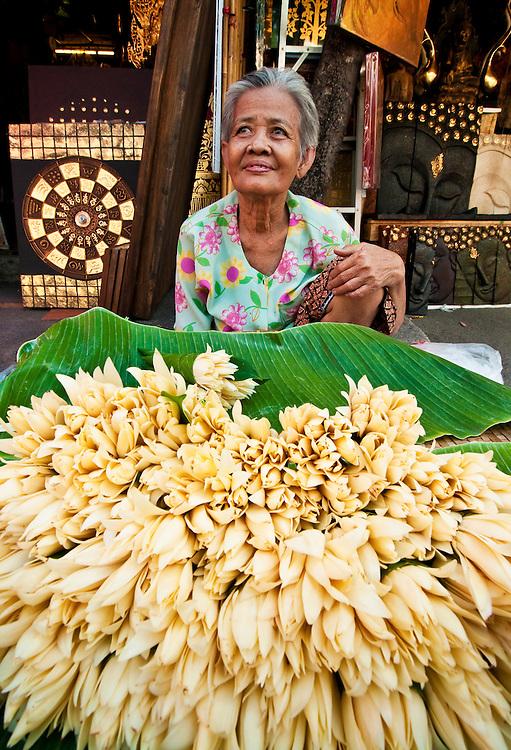 Woman selling flowers in Chatuchak Weekend Market in Bangkok, Thailand.