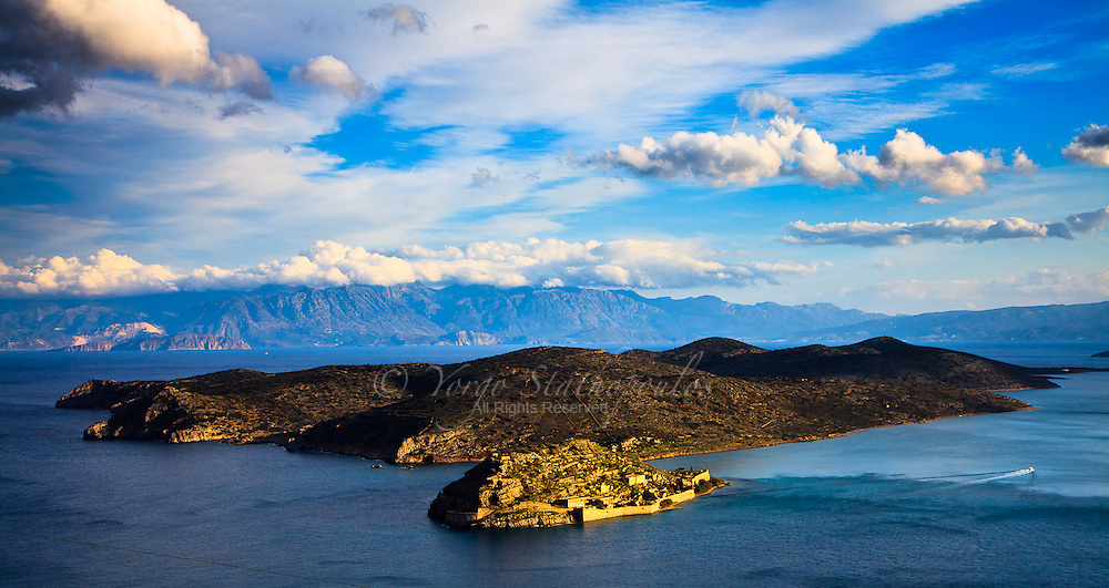 """The island of Spinalonga (official name: Kalidon) is located at the eastern section of Crete, in Lassithi prefecture, near the town of Elounda. The name of the island, Spinalonga, is Venetian, meaning """"long thorn"""", and has roots in the period of Venetian occupation. This location is also the setting for Victoria Hislop's bestselling novel The Island and Werner Herzog's experimental short film Last Words. The island was used as a leper colony, from 1903 to 1957. It is notable for being one of the last active leper colonies in Europe. The last inhabitant, a priest, left the island in 1962. .There were two entrances to Spinalonga, one being the lepers' entrance, a tunnel known as Dante's Gate. This was so named because the patients did not know what was going to happen to them once they arrived. However, once on the island they received food, water, medical attention and social security payments. Previously, such amenities had been unavailable to Crete's leprosy patients, as they mostly lived in the area's caves, away from civilization."""