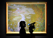 © licensed to London News Pictures. LONDON, UK.  13/06/11. A videographer films 'Nympheas' by Claude Monet (1840-1926) it is expected to fetch in excess of £17 million at auction on 21st June).Photo call at Christie's, London, for the unveiling of rarely seen masterpieces by Picasso, Michelangelo and Gainsborough before they are offered for sale. Photo credit should read Stephen Simpson/LNP
