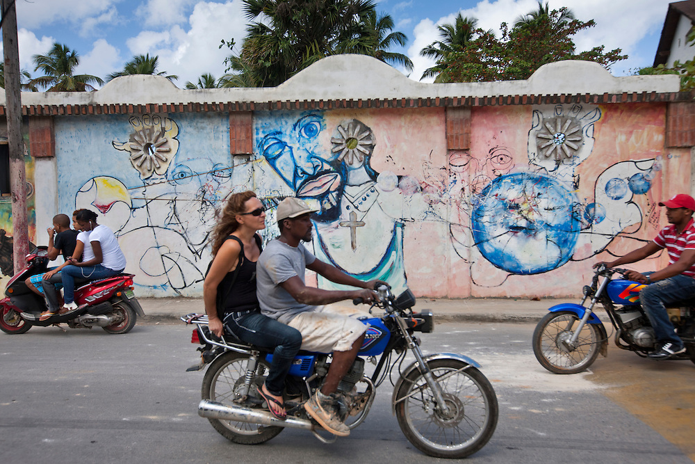 Dominican Republic, Las Terrenas, Motorcycle taxi carries young woman past religious mural through traffic in Caribbean resort town