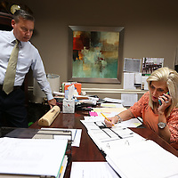Adam Robison   BUY AT PHOTOS.DJOURNAL.COM<br /> Kevin Seddon, Tupelo Furniture Market President, stands in Debbie Henry's office as she takes one of many phone calls as they prepare for the upcoming furniture market.