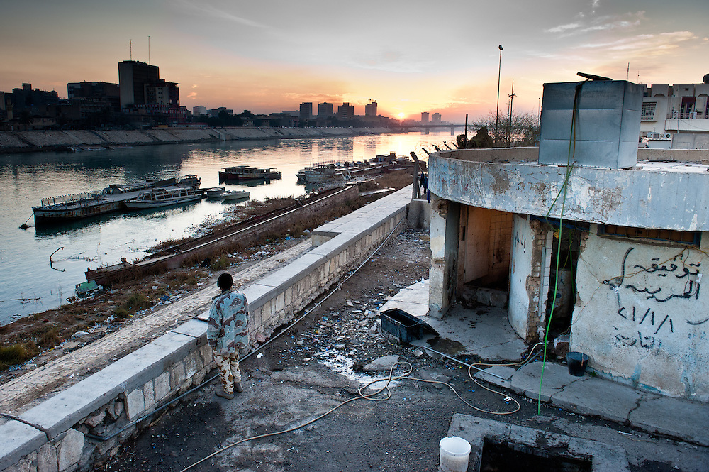 An Iraqi policeman looks out over rusting hulks of barges, remnants of a more propserous time, on the Tigris River in Baghdad.