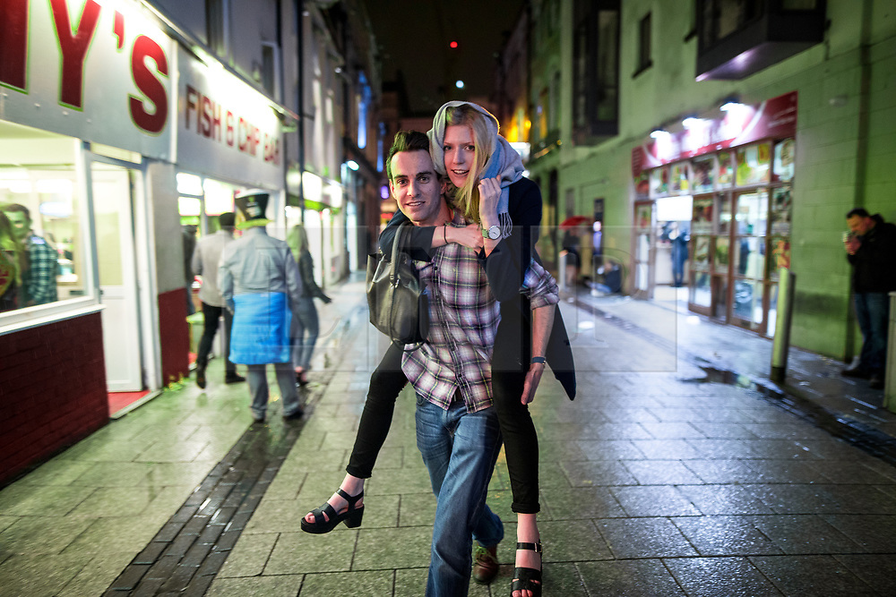 © Licensed to London News Pictures . 18/03/2017 . Cardiff , UK. A man carries a woman in his back along Caroline Street . Revellers on a windy and wet Saint Patrick's Day night out in Cardiff city Centre . Photo credit: Joel Goodman/LNP