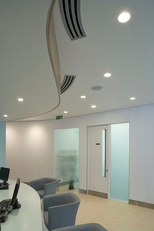 reception area of office with curved ceiling, chairs and computers and blurred figure walking through doorway