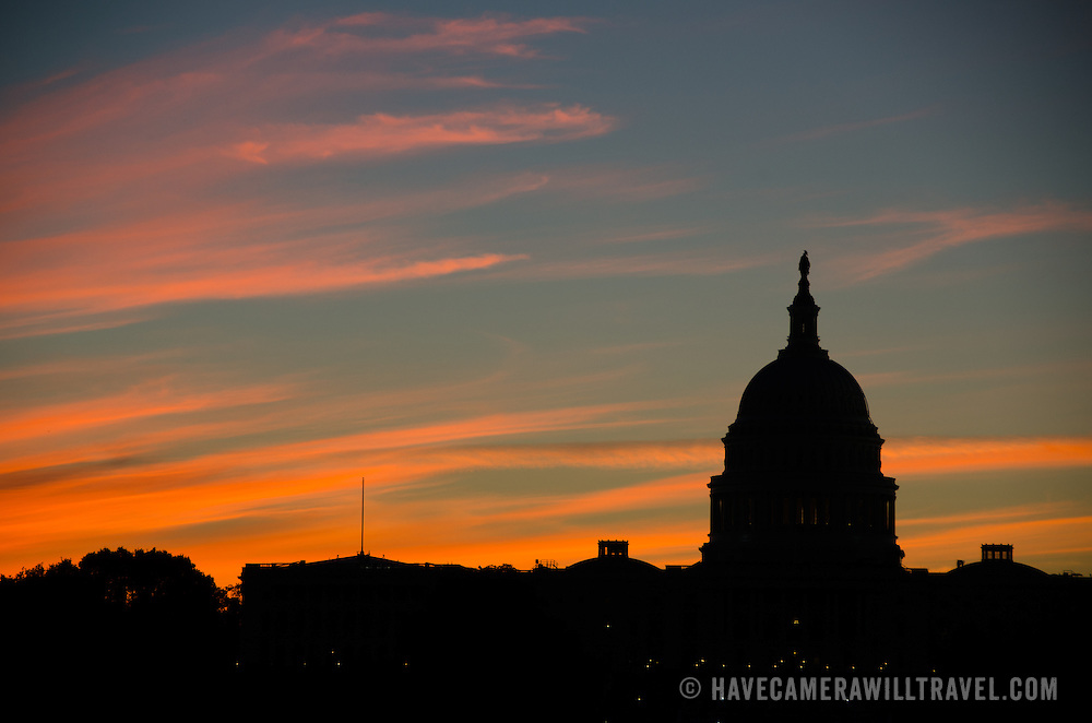 The predawn light colorfully illuminates clouds behind a silhouette of the US Capitol Building Dome (Congress).