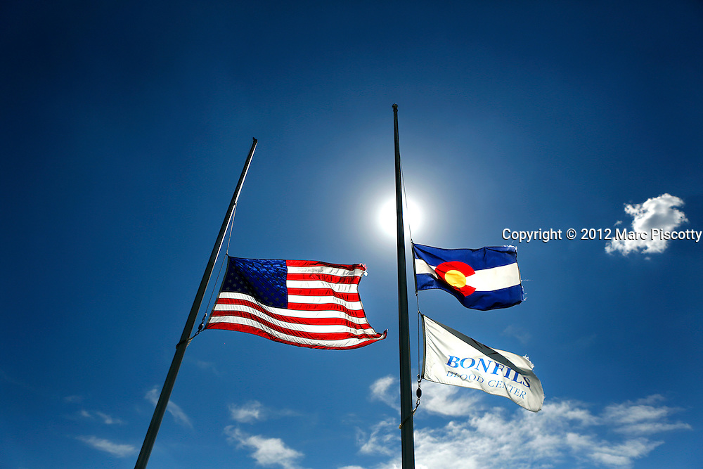 SHOT 7/21/12 3:51:42 PM - The American and Colorado state flag fly at half mast in honor of the victims of the Aurora theater shootings outside of the Bonfils Blood Center in Denver, Co. on Saturday July 21, 2012. James Eagan Holmes will face charges in the shootings that occurred on Friday July 20, 2012 in which twelve people were killed and another 58 were injured. (Photo by Marc Piscotty / © 2012)