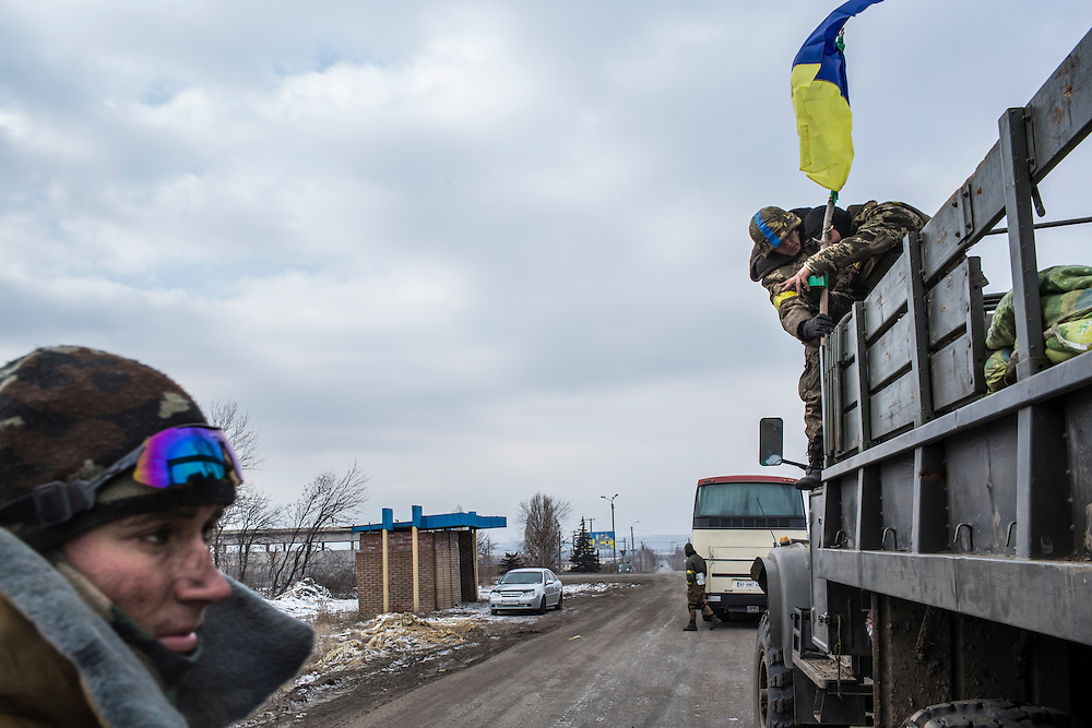 ARTEMIVSK, UKRAINE - FEBRUARY 19: Ukrainian soldiers from a unit based in Zaporizhia raise a Ukrainian flag on their truck after withdrawing from Debaltseve the previous day on February 19, 2015 in Artemivsk, Ukraine. Ukrainian forces started withdrawing from the strategic and hard-fought town of Debaltseve yesterday being effectively surrounded by pro-Russian rebels. (Photo by Brendan Hoffman/Getty Images) *** Local Caption ***