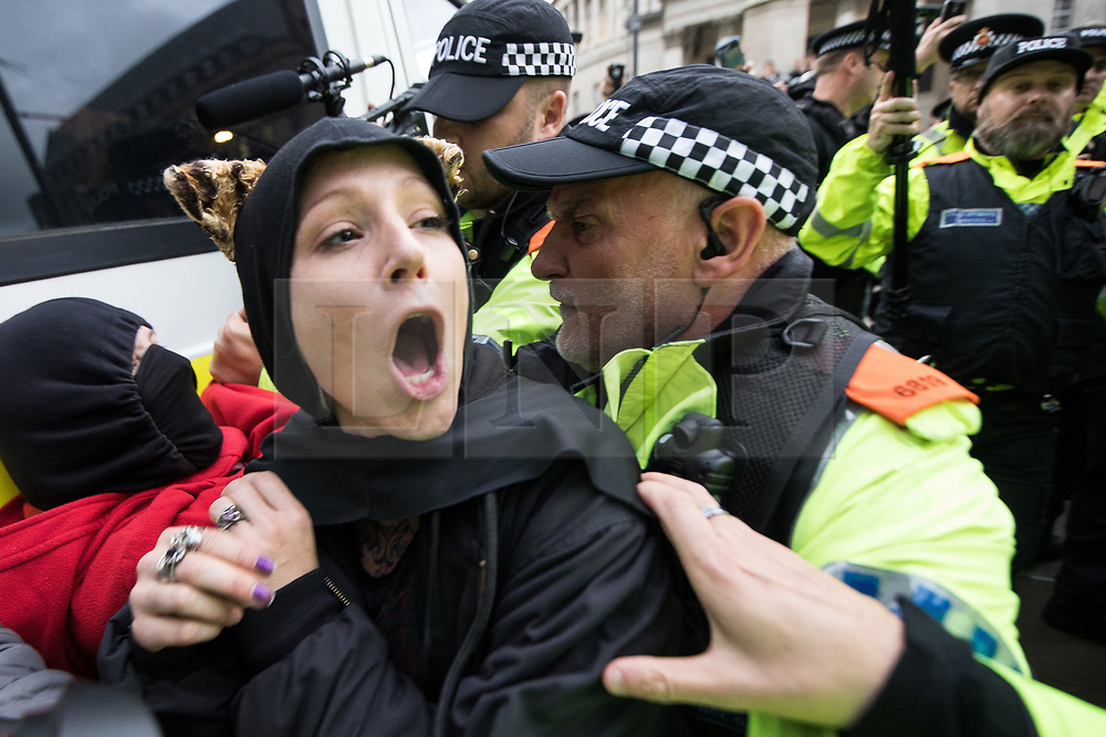 © Licensed to London News Pictures . 01/10/2017. Manchester, UK. Police push aside protesters who attempt to block them arresting wheelchair users amongst anti Tory protesters blocking tramtracks at St Peter's Square opposite the Midland Hotel . People take part in a demonstration against the Conservative Party in Manchester during the Conservative Party Conference , which is taking place at the Manchester Central Convention Centre . Photo credit: Joel Goodman/LNP