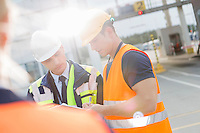 Male workers discussing over clipboard in shipping yard