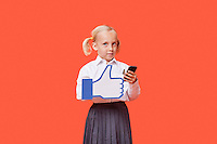 Portrait of a young schoolgirl with cell phone holding fake like button over orange background