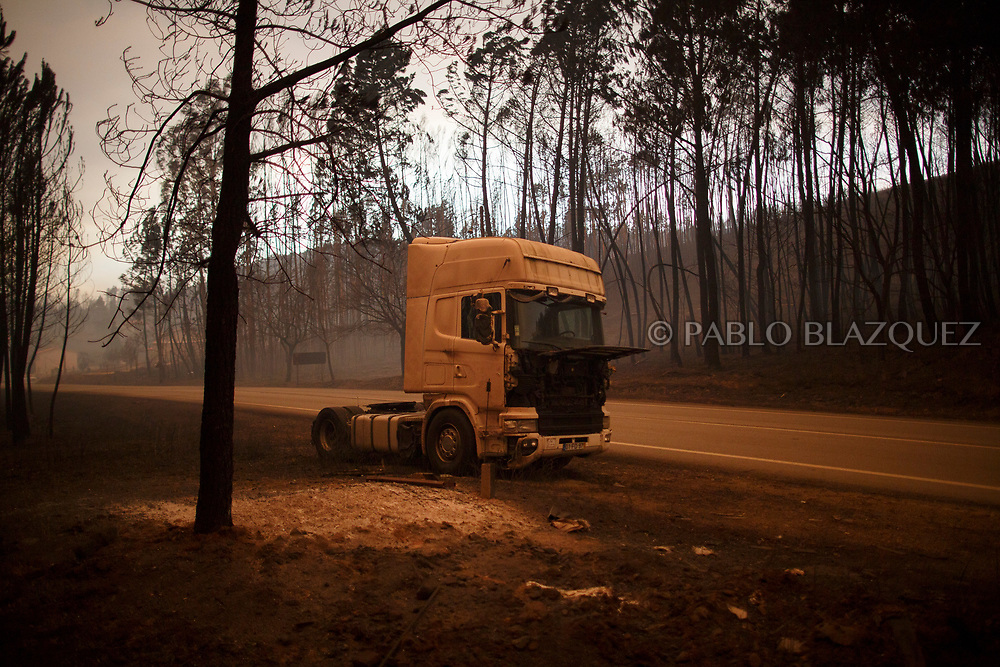 LEIRIA, PORTUGAL - JUNE 18:  A burned lorry stands on the side of the road after a wildfire took dozens of lives on June 18, 2017 near Castanheira de Pera, in Leiria district, Portugal. On Saturday night, a forest fire became uncontrollable in the Leiria district, killing at least 62 people and leaving many injured. Some of the victims died inside their cars as they tried to flee the area.  (Photo by Pablo Blazquez Dominguez/Getty Images)