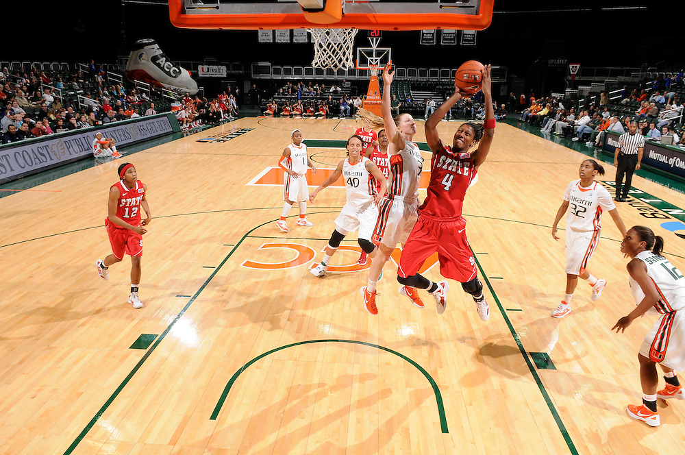 January 5, 2012: Tia Bell #4 of North Carolina State shoots past Stefanie Yderstrom #3 of Miami during the NCAA basketball game between the Miami Hurricanes and the North Carolina State Wolfpack at the BankUnited Center in Coral Gables, FL. The Hurricanes defeated the Wolfpack 78-68.