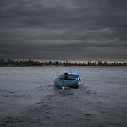 KHERSON, UKRAINE - March 17, 2014: Two men cross the Dnieper river by boat in Kherson, Ukraine. CREDIT: Paulo Nunes dos Santos