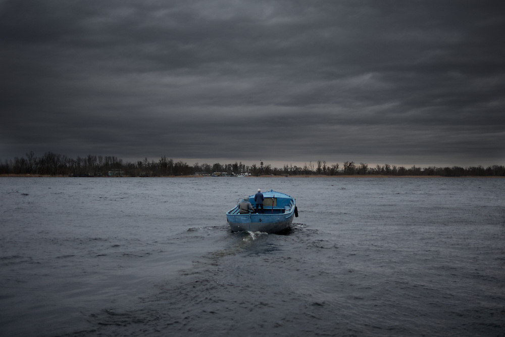 Two men cross the Dnieper river by boat in Kherson, Ukraine.