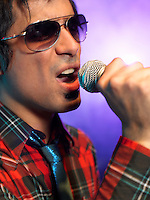 Young Man Singing into microphone on stage at Concert close up