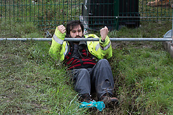 Harefield, UK. 8 February, 2020. An environmental activist crawls through a ditch under a road closure implemented by HS2 engineers on Harvil Road in the Colne Valley to facilitate tree felling works for the high-speed rail project. Environmental activists based at a series of wildlife protection camps in the area prevented the tree felling works for the duration of the weekend for which they were scheduled.
