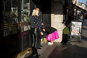 A lady wearing a pink dress stoops to stub out a cigarette, on 25th October 2018, in Piccadilly, London, England.