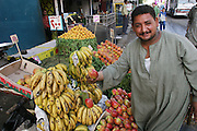 A proud Cairo fruit stand owner shows off his produce. Cairo, Egypt.
