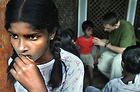 MISSION OF COMPASSION (GAZE)<br /> Sewwamdo Shamali lost her father in the Tsunami and her mother who has no source of income delivered her and her two younger sisters Erindi, 12, and Madushani, 8, to the Agape orphanage.  She stands to the side of the cottage that houses the girls while Dr. Greg Rurik of Gig Harbor, Wash. Tends to their medical needs.