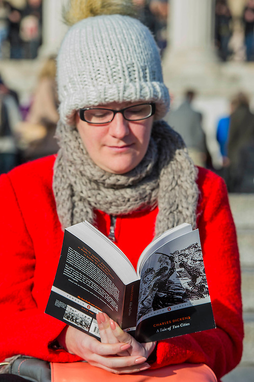 A woman reads a Tale of Two cities while she waits. Je suis Charlie/I am Charlie - A largely silent (with the occasional rendition of the Marseileus)gathering in solidarity with the march in Paris today.  Trafalgar Square, London, UK 11 Jan 2015