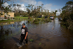 September 11, 2017 - Collier County, Florida, U.S. - HERMILO MUNOZ CASTILLO wades down a flooded street to check on his home in southern Collier County. He said there was little to nothing to salvage from his home upon inspection. Hurricane Irma swept through south Florida leaving behind a trail of debris, flooding and power outages. (Credit Image: © Loren Elliott/Tampa Bay Times via ZUMA Wire)
