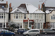 Snow covered rooftops of south London residential houses, some with adequate and others poorly insulated.
