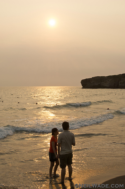 A couple holds hands in the surf as the sun sets on Cijin Island, Kaohsiung.