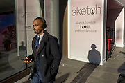 A man listens through headphones while walking past 'Sketch', a gastro-gallery on Conduit Street, on 20th January 2020, in London, England.