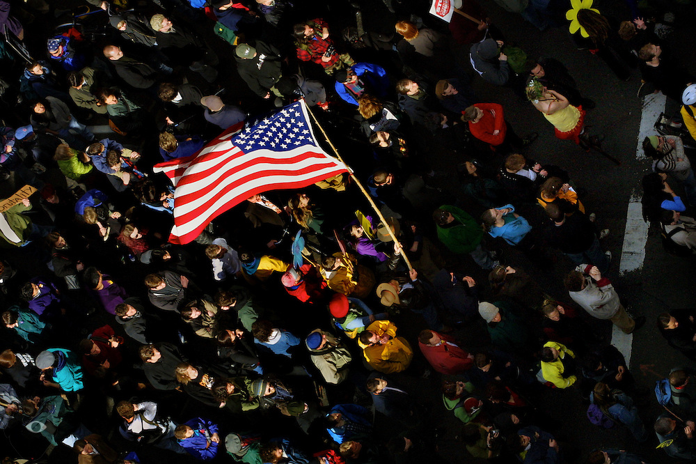 A large flag catches the light above the multitude of individuals traveling in a Portland May Day protest.