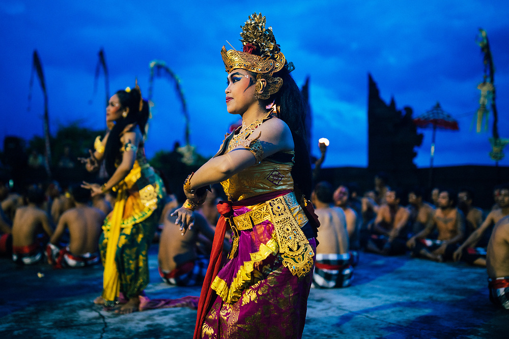 A traditional kecak performance overlooking the ocean at dusk at Ulawatu Temple in Bali, Indonesia.