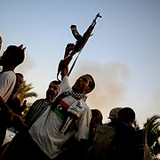 A group of rebel fighters celebrate the successful take of Muammar Gaddafi's Bab Al Azizia compound in Tripoli