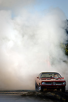 A participant in the River City Rod Run burnout session is followed by a cloud of smoke Friday.