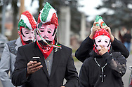 Middletown, New York - A man wearing a mask looks at his cell phone outside St. Joseph's Church before marching through the city during the festival of Nuestra Senora de Guadalupe on Sunday, Dec. 9, 2012.