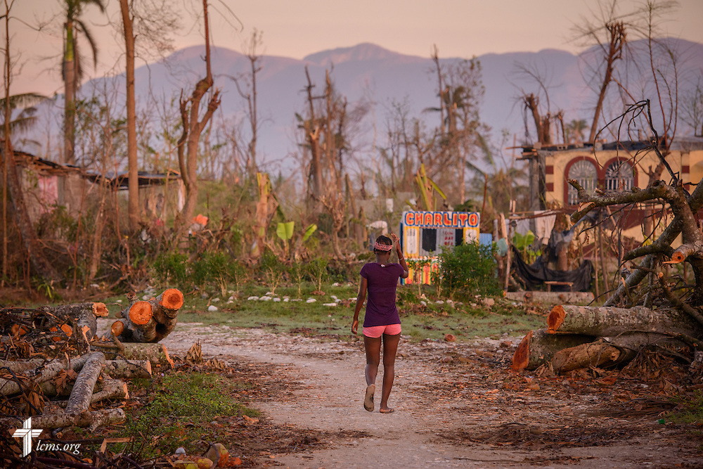 A young woman walks past destruction caused by Hurricane Matthew on Wednesday, Oct. 12, 2016, in a rural area of Les Cayes, Haiti. LCMS Communications/Erik M. Lunsford