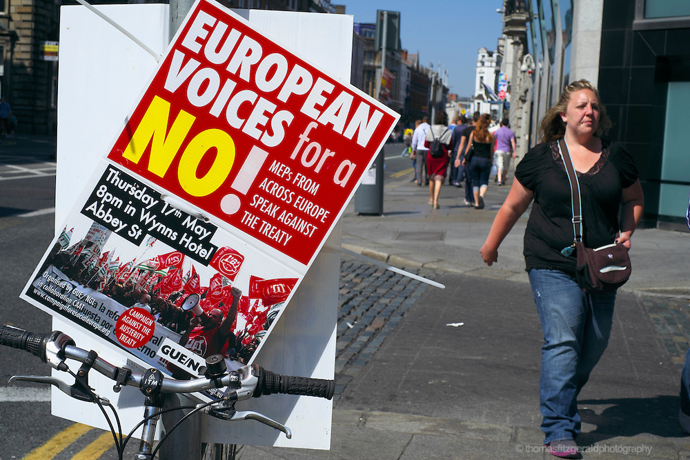 A poster urging a No vote in the upcoming fiscal treaty referendum hangs on a pole on Dublin's Dame Street while passers by continue about their business