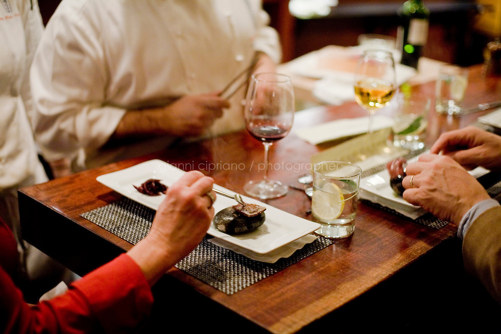 """11 December, 2008. New York, NY. Customers of a special seating enjoy a self-cooked kobe beef on hot stone in the open kitchen of Waldy Malouf at the Beacon restaurant. NOTE: the cook in the background is not Wandy. Waldy Malouf is """"on stage"""" for a small birthday party of six people in the open kitchen of Beacon's dining room, a New York restaurant. Several restaurants offer special seatings with their celebrity chefs.<br /> <br /> ©2008 Gianni Cipriano for The New York Times<br /> cell. +1 646 465 2168 (USA)<br /> cell. +1 328 567 7923 (Italy)<br /> gianni@giannicipriano.com<br /> www.giannicipriano.com"""