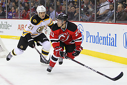 Jan 4, 2012; Newark, NJ, USA; New Jersey Devils left wing Mattias Tedenby (21) and Boston Bruins defenseman Andrew Ference (21) race for the loose puck during the second period at the Prudential Center.