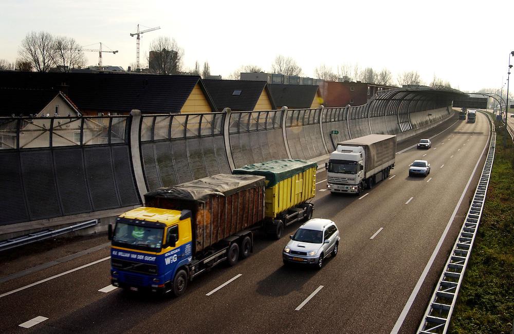 Nederland, Dordrecht, 2 dec 2004.Geluidsscherm tussen woningen en A16. Geluidsoverlast, geluidshinder.snelweg, lawaai, verkeer, luchtkwaliteit..Foto (c) Michiel Wijnbergh/HH