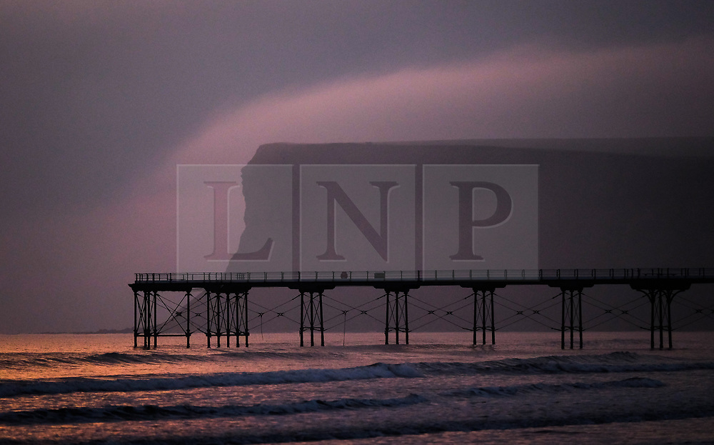 © Licensed to London News Pictures. <br /> 27/03/20167. <br /> Saltburn by the Sea, UK.  <br /> <br /> A band of fog stretches over the top of cliffs at Huntcliff in Saltburn by the Sea.<br /> <br /> Photo credit: Ian Forsyth/LNP
