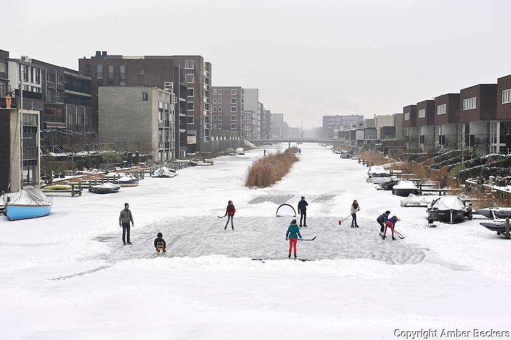 Nederland, Amsterdam, 26 januari 2013.Kinderen op IJburg hebben een stukje ijs sneeuwvrij gemaakt en spelen ijshockey..Children play icehockey on IJburg.