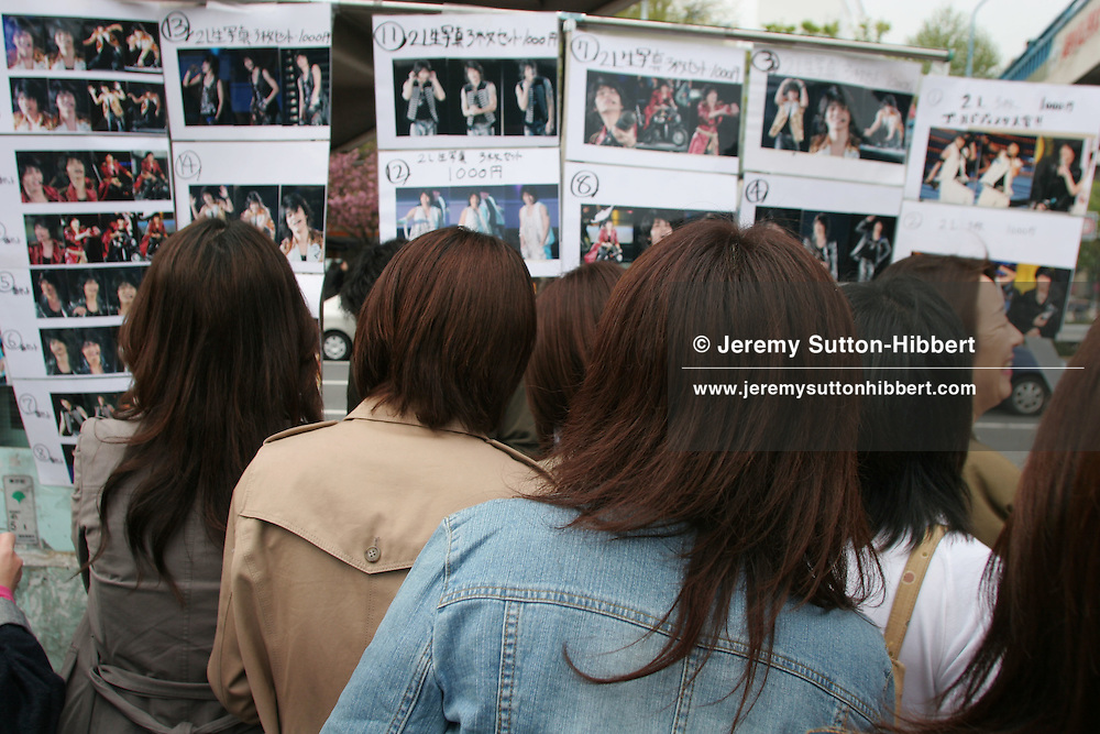 Japanese women and girls, with their black hair dyed brown, looking at photos for sale of their favourite male celebrities, in Harajuku district of Tokyo, Japan.