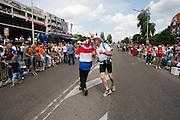 Wandelaars van de Nijmeegse Vierdaagse feesten op de laatste dag op de Via Gladiola, zoals de Sint Annastraat is omgedoopt tijdens het wandelevenement.