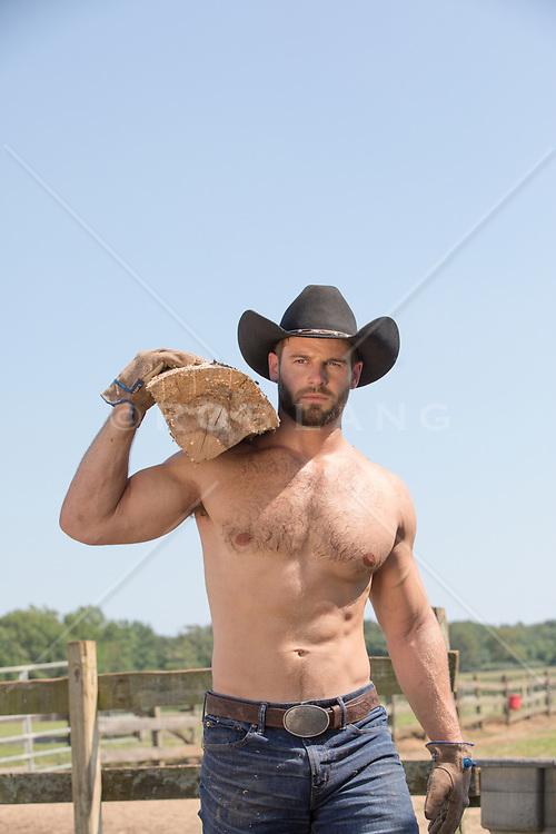 rugged shirtless cowboy carrying wood